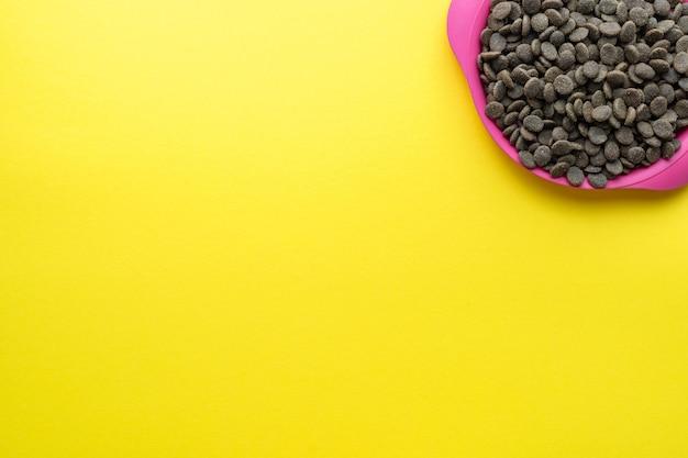 Uma tigela de comida de cachorro em um fundo amarelo no canto superior direito. camada plana, vista superior. espaço para texto.