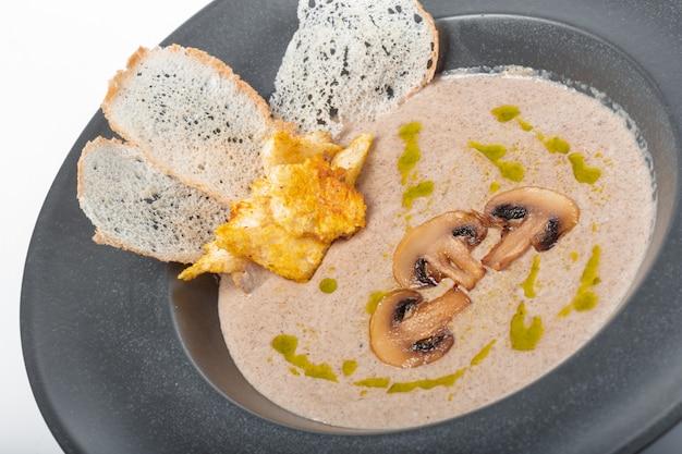 Uma tigela de creme caseiro delicioso de sopa de cogumelos