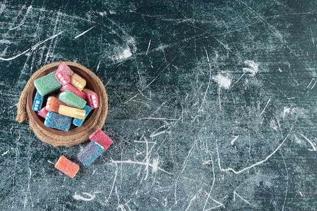 Uma tigela de doces coloridos em um tripé, na mesa mista.