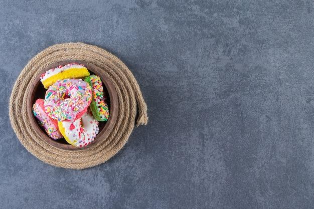 Uma tigela de donuts em um tripé, no fundo de mármore.