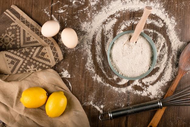 Uma tigela de farinha com colher de pau, ovos e limões