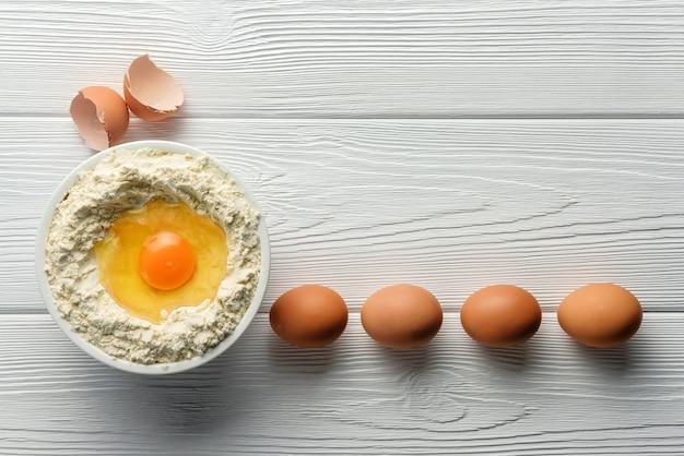 Uma tigela de farinha e vários ovos em uma mesa de madeira. conceito de cozimento.