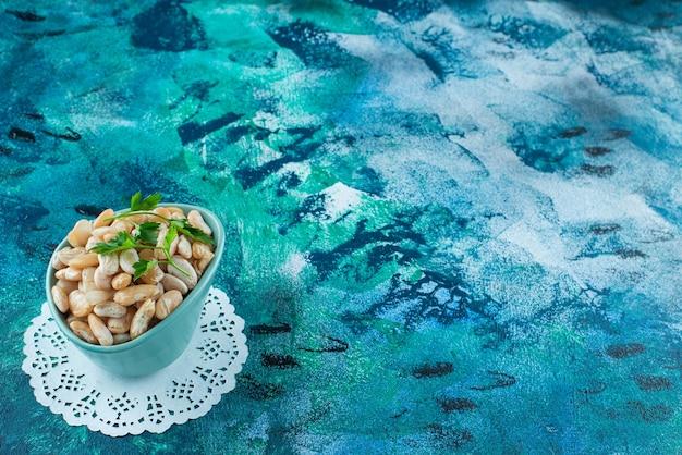 Uma tigela de feijão branco com salsa, no fundo azul.