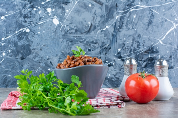 Uma tigela de feijão cozido e tomate vermelho fresco com salsa em uma toalha de mesa.