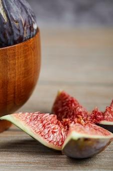 Uma tigela de figos pretos e fatias de figos em uma mesa de madeira, close-up. foto de alta qualidade