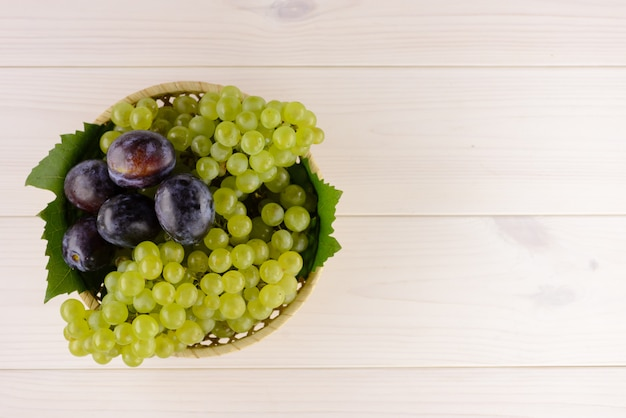 Uma tigela de frutas saborosas de verão na mesa de madeira branca
