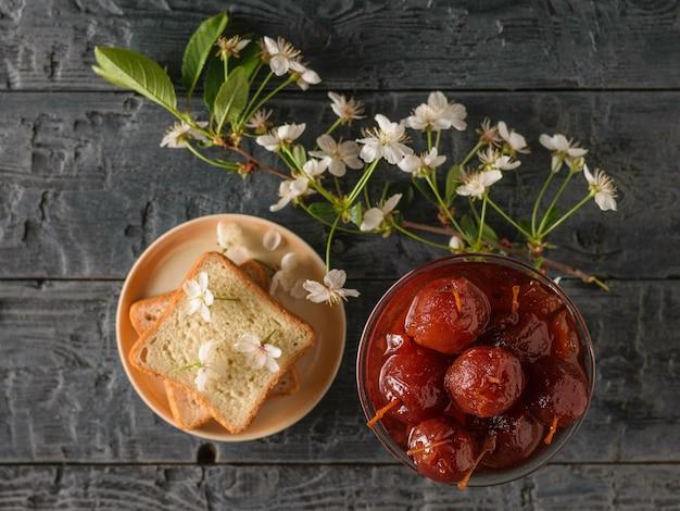 Uma tigela de geleia de maçã, pão e um ramo de flores em uma mesa escura. doces caseiros de acordo com receitas antigas. postura plana.