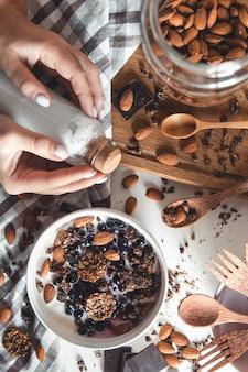 Uma tigela de granola caseira crocante com leite de amêndoa em uma mesa.