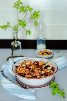Uma tigela de granola com nozes, chocolate e cranberries secas, uma garrafa de leite, uma tigela pequena com nozes, toalha e galho verde