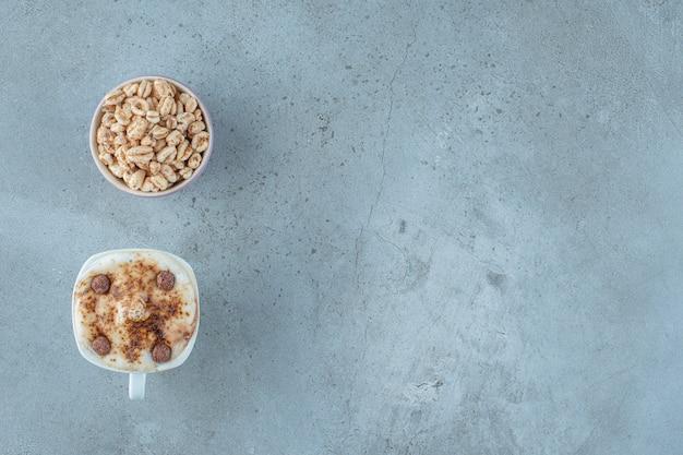 Uma tigela de granola e uma xícara de cappuccino, sobre o fundo azul.