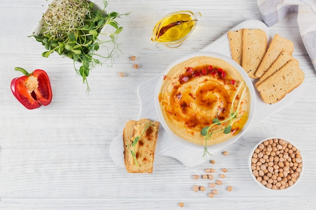 Uma tigela de homus caseiro de grão de bico com azeite, pão crocante, microgreen e páprica defumada na superfície de madeira branca