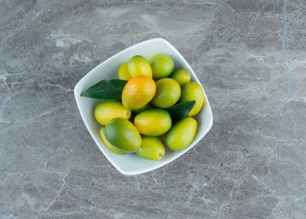 Uma tigela de kumquat verde, sobre a mesa de mármore.