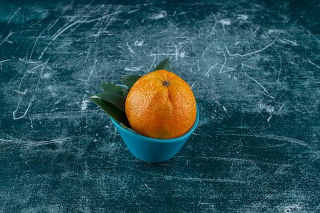 Uma tigela de laranja com folhas, na mesa de mármore.