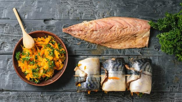 Uma tigela de legumes cozidos no vapor, a carcaça da cavala e os três peixes preparados para assar. postura plana.