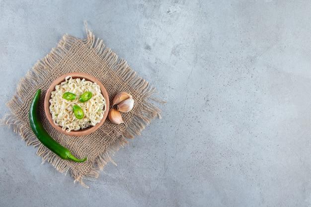 Uma tigela de macarrão ao lado de pimenta e alho sobre uma serapilheira, no fundo de mármore.