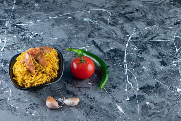 Uma tigela de macarrão com carne ao lado de vegetais, no fundo de mármore.