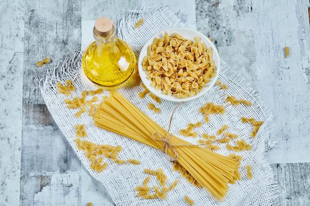 Uma tigela de macarrão cru e espaguete com óleo e toalha de mesa.