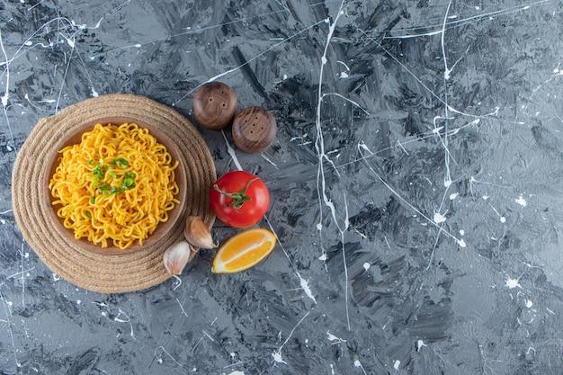 Uma tigela de macarrão em um tripé ao lado de tomate, limão e alho, sobre o fundo de mármore.