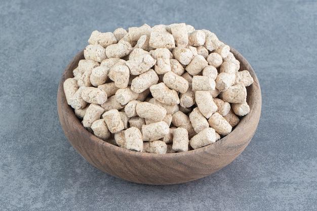 Uma tigela de madeira cheia de cereais crocantes de centeio.