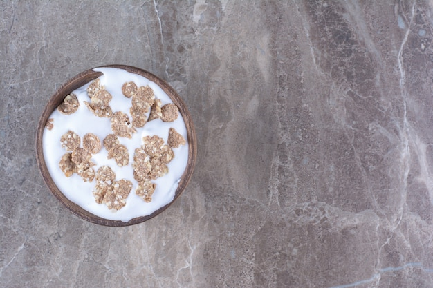 Uma tigela de madeira cheia de cereais saudáveis com leite no café da manhã.