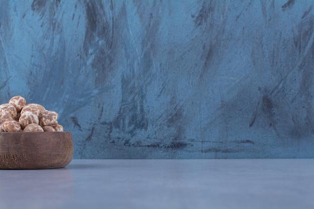 Uma tigela de madeira cheia de cereais saudáveis em uma superfície cinza