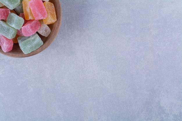 Uma tigela de madeira cheia de doces de feijão coloridos em uma superfície cinza