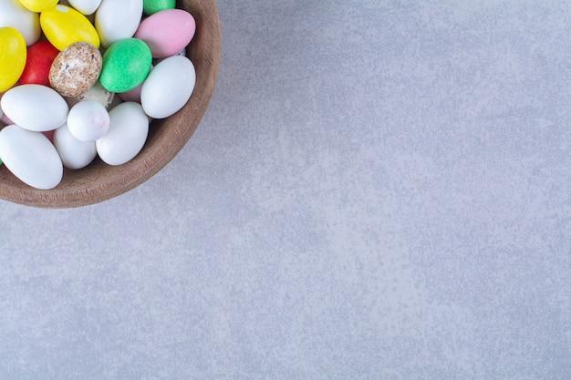 Uma tigela de madeira cheia de doces de feijão coloridos na mesa cinza.