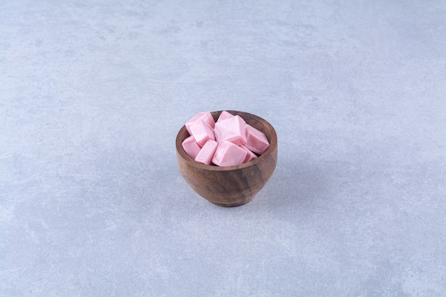 Uma tigela de madeira cheia de doces rosa pastila.