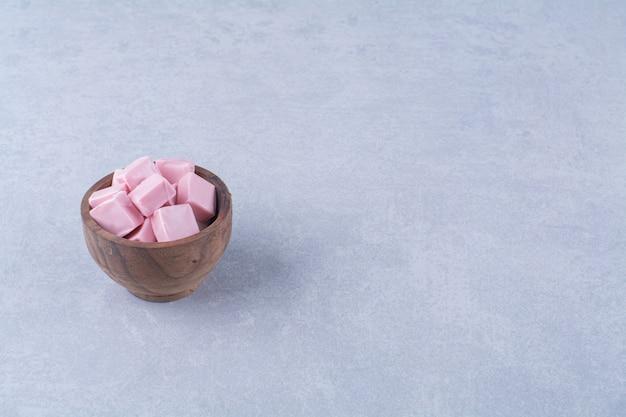 Uma tigela de madeira cheia de doces rosa pastila