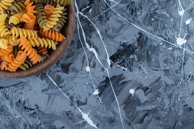 Uma tigela de madeira cheia de macarrão multicolorido sobre um fundo cinza.