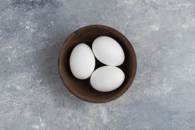 Uma tigela de madeira cheia de ovos de galinha brancos frescos em um fundo de mármore.