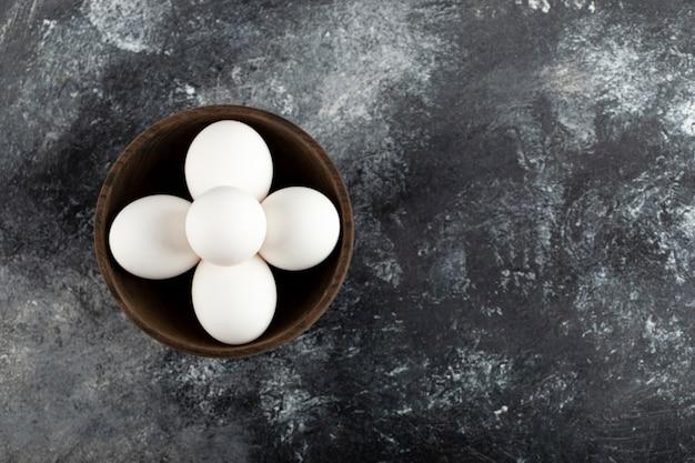Uma tigela de madeira cheia de ovos de galinha crus.