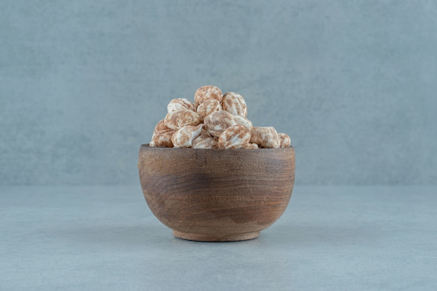Uma tigela de madeira cheia de um delicioso pão de mel doce na superfície branca