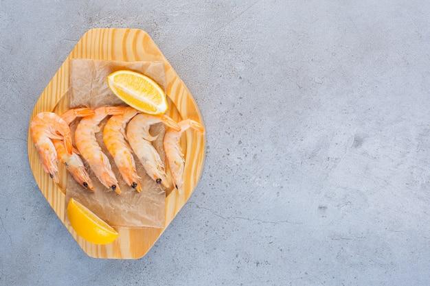 Uma tigela de madeira com deliciosos camarões com fatias de limão em uma superfície de pedra