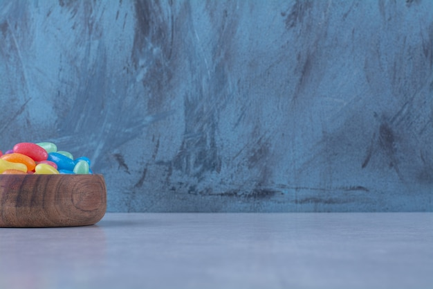 Uma tigela de madeira com doces coloridos de geleia