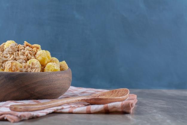 Uma tigela de madeira com flocos de milho saudáveis e uma colher de pau vazia.