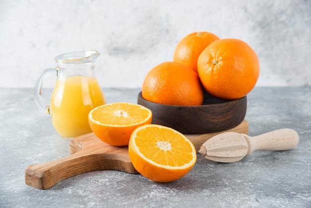 Uma tigela de madeira com frutas frescas de laranja e uma jarra de vidro com suco.
