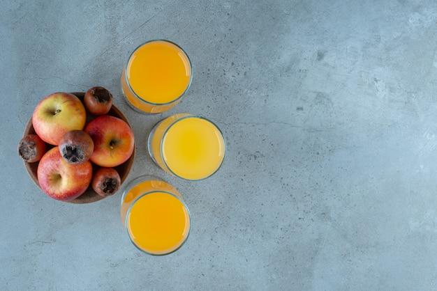 Uma tigela de madeira com maçãs com copos de suco de laranja.