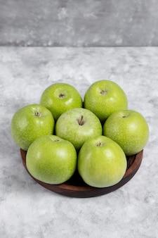 Uma tigela de madeira com maçãs verdes frescas na pedra