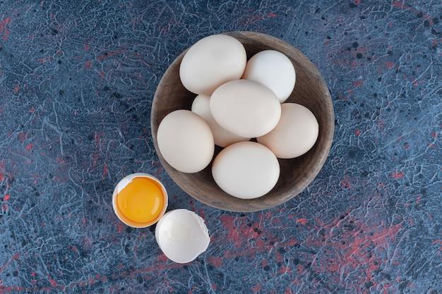 Uma tigela de madeira com ovos de galinha crus frescos.
