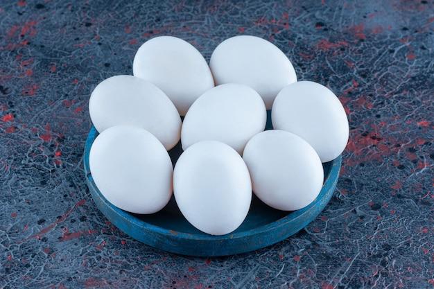 Uma tigela de madeira com ovos de galinha crus