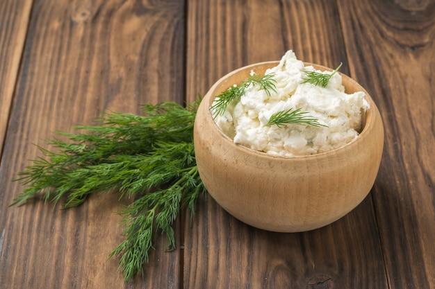 Uma tigela de madeira com queijo cottage e um monte de endro em uma mesa de madeira. o conceito de alimentação saudável. creme de coalhada