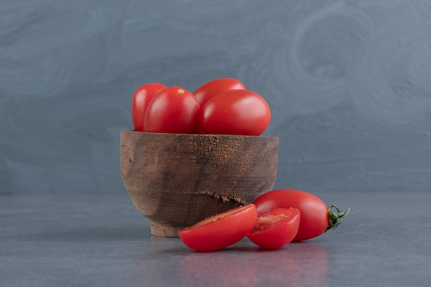 Uma tigela de madeira com tomates-cereja vermelhos
