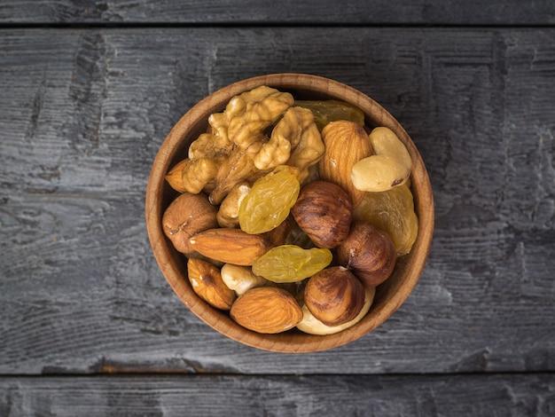 Uma tigela de madeira com uma mistura de nozes e frutas secas em uma mesa de madeira preta. comida vegetariana natural e saudável. a vista do topo.