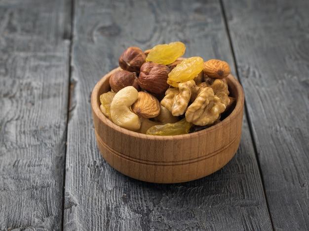 Uma tigela de madeira com uma mistura de nozes e frutas secas em uma mesa de madeira preta. comida vegetariana natural e saudável.