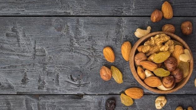 Uma tigela de madeira com uma mistura de nozes e frutas secas em uma tigela de madeira sobre uma mesa preta. comida vegetariana natural e saudável. postura plana.