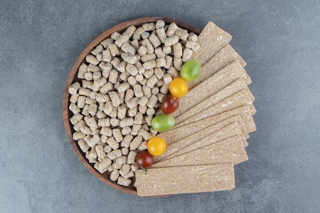 Uma tigela de madeira de cereais crocantes de centeio com tomates coloridos.