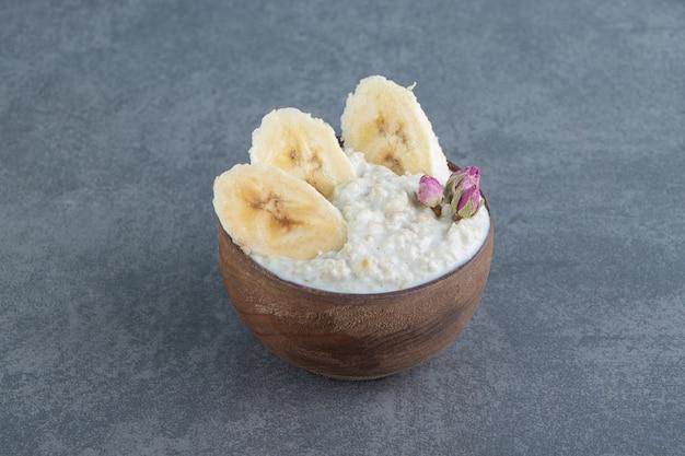 Uma tigela de madeira de mingau de aveia com fatias de banana.