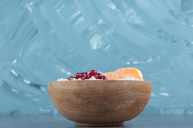 Uma tigela de madeira de mingau de aveia com tangerina e romã.
