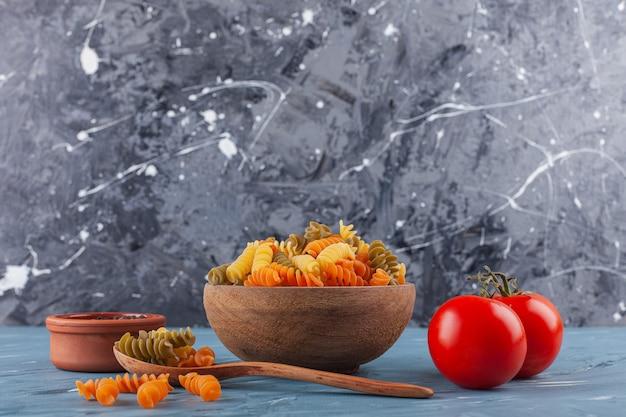 Uma tigela de massa espiral crua multicolorida com tomates vermelhos frescos e especiarias.